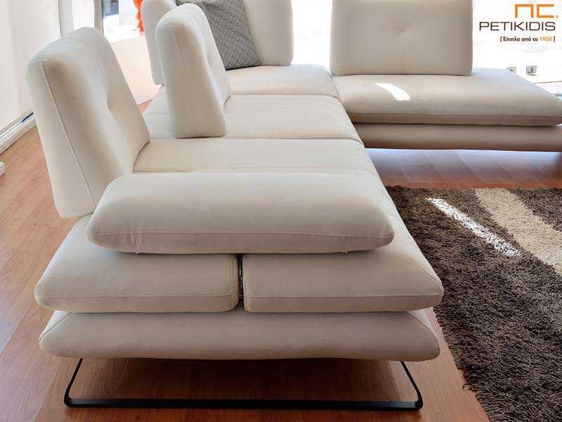 Σαλόνι γωνία Albert με μηχανισμούς στην πλάτη και στα μπράτσα, μεταλλικά πόδια και διακοσμητικό τζάμι στην άκρη του ανάκλυνδρου. Το ύφασμα σε λευκό χρώμα είναι αλέκιαστο και αδιάβροχο. Λεπτομέρεια