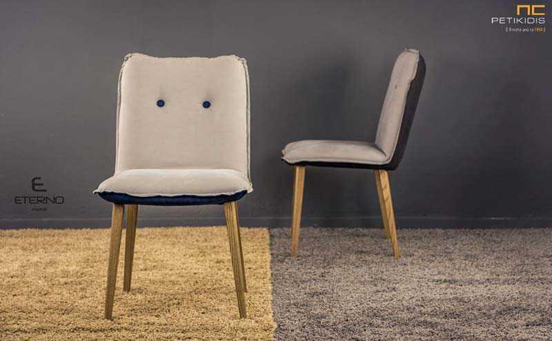 Καρέκλα Cube με μασίφ ξύλινα πόδια. Το ύφασμα είναι σε δύο χρώματα σε γκρι και μπλε αδιάβροχο και αλέκιαστο. Ιδιαίτερο στοιχείο είναι τα κουμπιά στην πλάτη που δίνουν μια πιο ρομαντική αίσθηση.