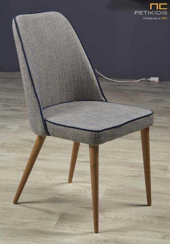 Καρέκλα Magata με ξύλινα πόδια και ύφασμα στο κάθισμα και την πλάτη σε γκρι χρώμα.Διαθέτει λεπτομέρειες με σκούρο γκρι ρέλι για να τονίσει περισσότερο το σχήμα της.