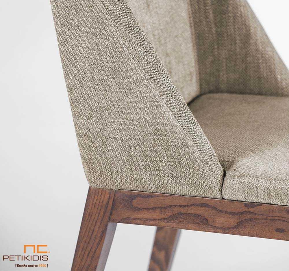 Καρέκλα Malta με μασίφ ξύλινα πόδια. Το ύφασμα στην πλάτη και στο κάθισμα είναι σε γκρι μπεζ τόνους και σχεδιασμό που αγκαλιάζει το σώμα για μεγαλύτερη άνεση. Λεπτομέρεια.