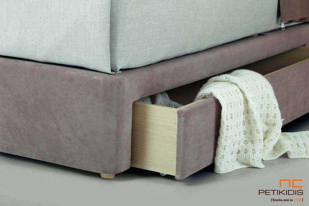 Υφασμάτινο κρεβάτι Cecil της Linea Strom σε καφέ μονόχρωμο ύφασμα και μαξιλάρες αποσπώμενες σε μπεζ καφέ λουλούδια.Το ύφασμα είναι αποσπώμενο από το κεφαλάρι. Λεπτομέρεια συρταριού βάσης.