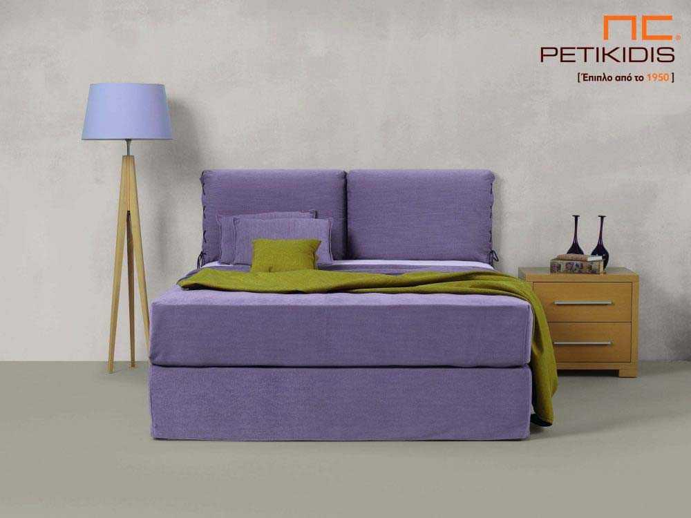 Υφασμάτινο κρεβάτι Joys της Linea Strom σε μοβ ύφασμα μονόχρωμο και λεπτομέρεια δεσίματος στις μαξιλάρες του κεφαλαριού. Το ύφασμα είναι αποσπώμενο και από τη βάση και από το κεφαλάρι για εύκολο καθάρισμα.