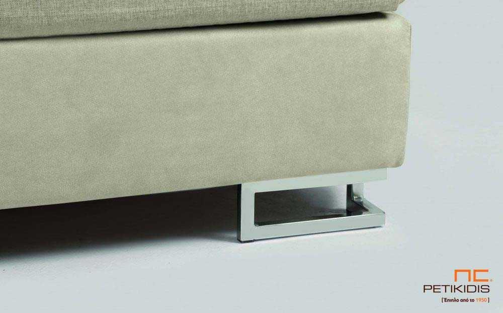 Υφασμάτινο κρεβάτι Milena της Linea Strom σε ύφασμα μπεζ μονόχρωμο αλέκιαστο και αδιάβροχο και σχέδια στις μαξιλάρες του κεφαλαριού. Το ύφασμα αφαιρείται από την βάση και το κεφαλάρι για εύκολο καθάρισμα. Λεπτομέρεια ποδιού βάσης.