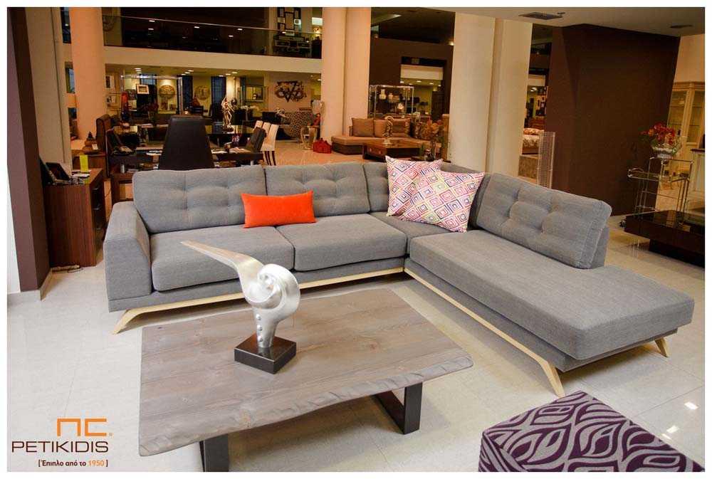 Σαλόνι γωνία Sixty με ξύλινη βάση και καπιτονέ ύφασμα στα μαξιλάρια της πλάτης σε γκρι αδιάβροχο ύφασμα και χρωματιστά διακοσμητικά μαξιλάρια.