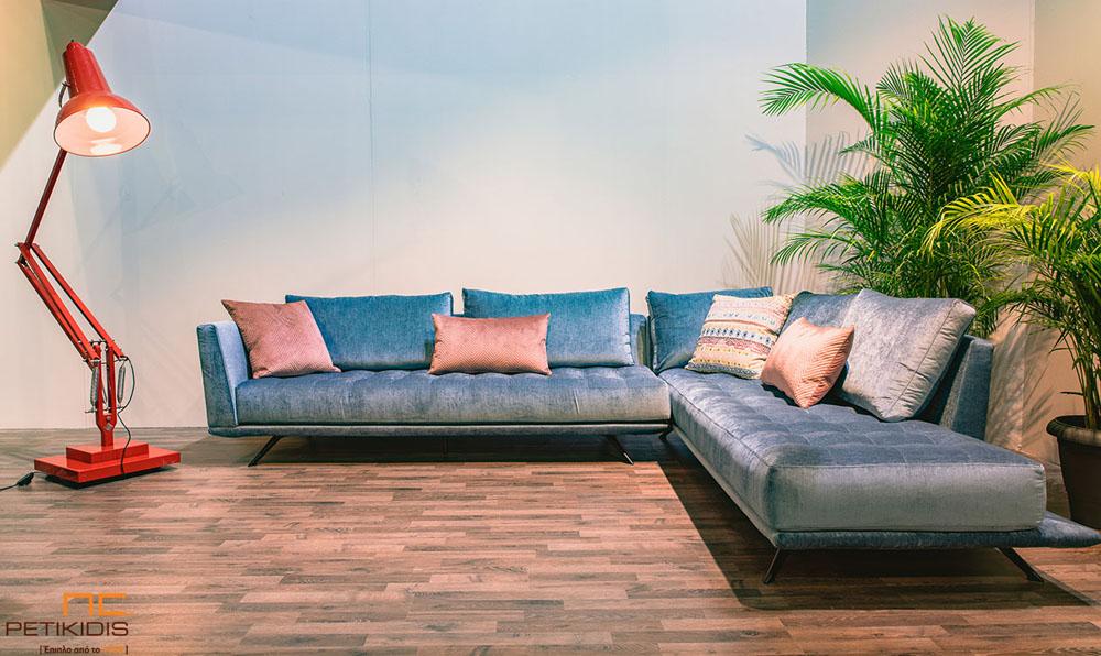 Σαλόνι γωνία Velvet με μεταλλικά πόδια και καπιτονέ μαξιλάρι στο κάθισμα. Το ύφασμα είναι σε μπλε αποχρώσεις σε βελούδο αδιάβροχο και διακοσμητικά μαξιλάρια σε κοραλί χρώμα.