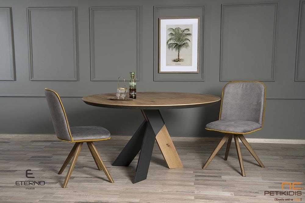Τραπέζι ροτόντα Flex από ξύλο ρουστίκ δρυς με λεπτομέρειες στα πόδια λάκα. Καρέκλα Libre με ύφασμα αλέκιαστο και αδιάβροχο.