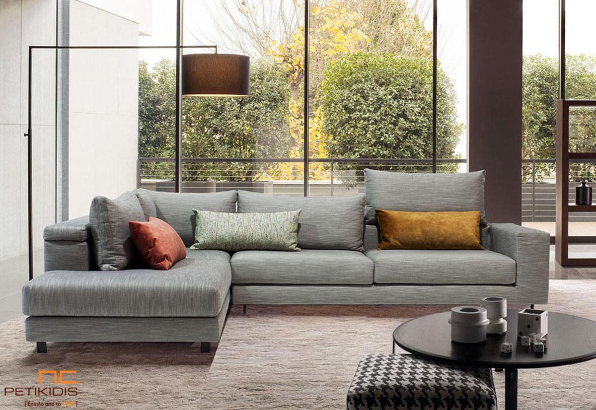 Σαλόνι γωνία Nouovo με δυνατότητα να τοποθετηθεί το μαξιλάρι της πλάτης για μεγαλύτερη ανάπαυση. Το ύφασμα είναι σε γκρι αποχρώσεις και διαθέτει χρωματιστά διακοσμητικά μαξιλάρια.