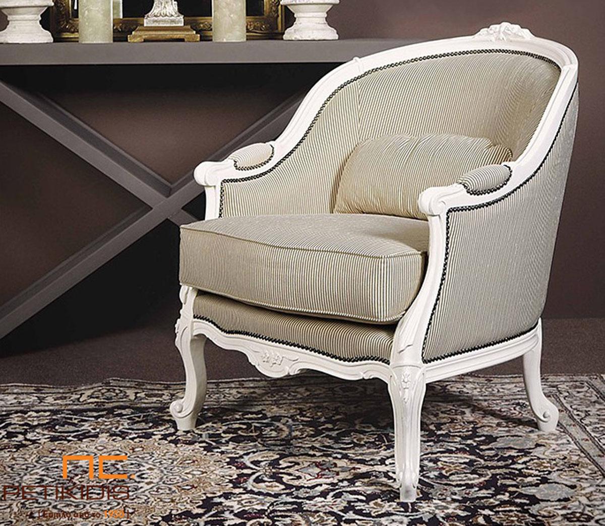 Πολυθρόνα Frida σε κλασική γραμμή με λεπτομέρειες ξύλου σε λευκή πατίνα. Το ύφασμα είναι σε εκρού αποχρώσεις με λεπτή ρίγα και διαθέτει διακοσμητικό μεταλλικό καμπαρά.